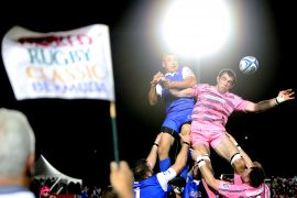 Men jump to catch a ball in a rugby match