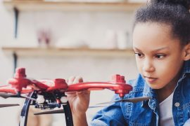 Little black girl playing with a drone