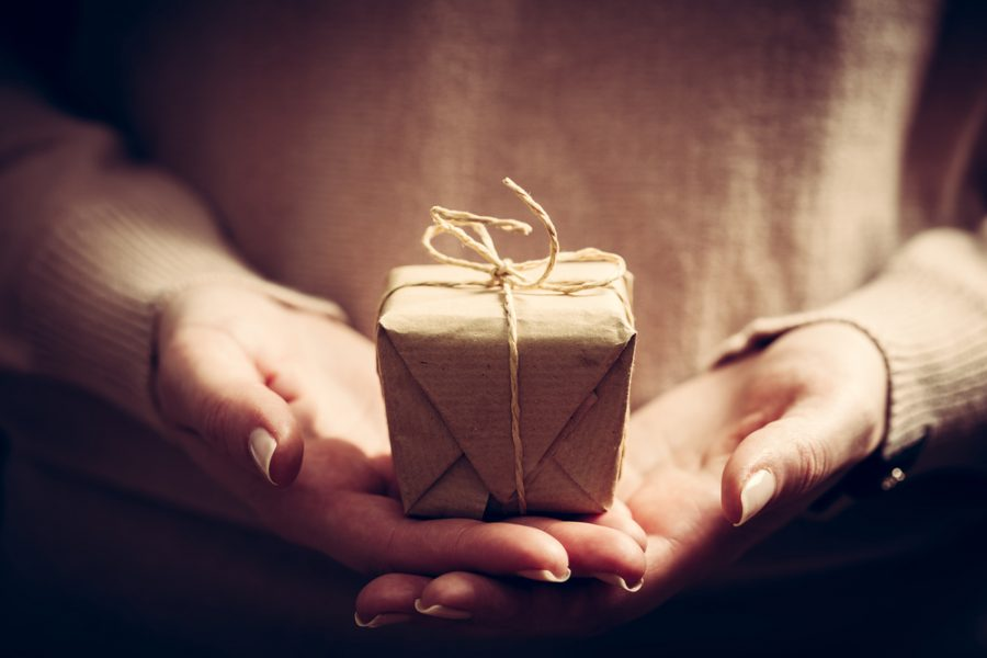 a women's hand holding a gift wrapped in recycled wrapping paper and twine