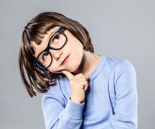 Little brunette girl with glasses thinking